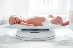 Newborn Girl In Diaper Lying On A Baby Scale