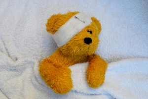 Sick Teddy laying in bed, with a bandage across his head