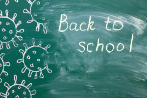 White chalk writing on a green chalkboard - back to school close-up and copy space.