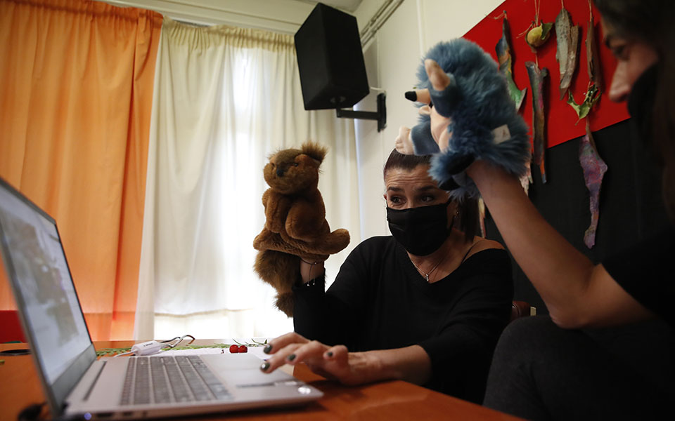 Teachers Aphrodite Tzevelekou, left, and Sofia Galiotou perform live an online puppet show for students at a kindergarten in Athens, Thursday, Nov. 19, 2020. Most other European countries have vowed to keep schools open, but the pandemic has hit Greece hard for the first time in recent weeks following a successful lockdown in the spring, overwhelming hospitals in parts of the country. State television is making and broadcasting lessons, while teachers sit in empty classrooms talking to remote students. Despite some problems, they say it keeps children in touch with their schools. (AP Photo/Thanassis Stavrakis)