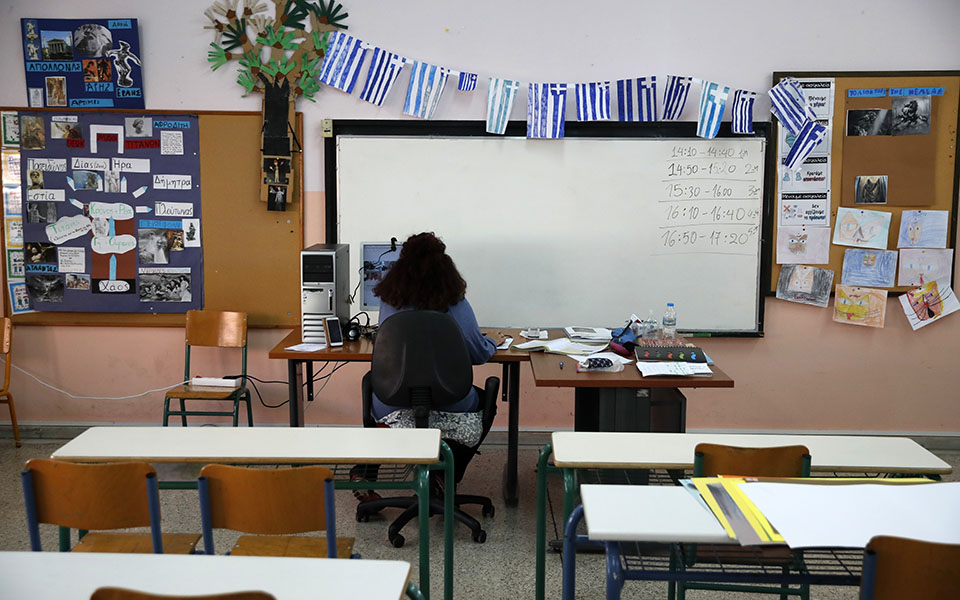 Teacher Katerina Papageorgiou gives an online lesson to C class students in an empty classroom of elementary school in Athens, Friday, Nov. 20, 2020. Most other European countries have vowed to keep schools open, but the pandemic has hit Greece hard for the first time in recent weeks following a successful lockdown in the spring, overwhelming hospitals in parts of the country. State television is making and broadcasting lessons, while teachers sit in empty classrooms talking to remote students. Despite some problems, they say it keeps children in touch with their schools. (AP Photo/Thanassis Stavrakis)
