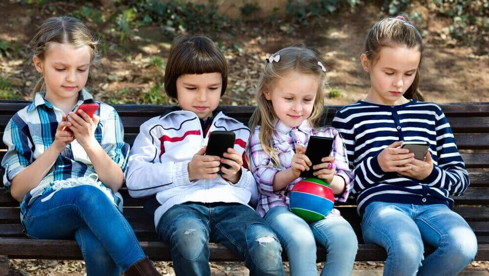 Four-children-on-a-bench-on-their-phones