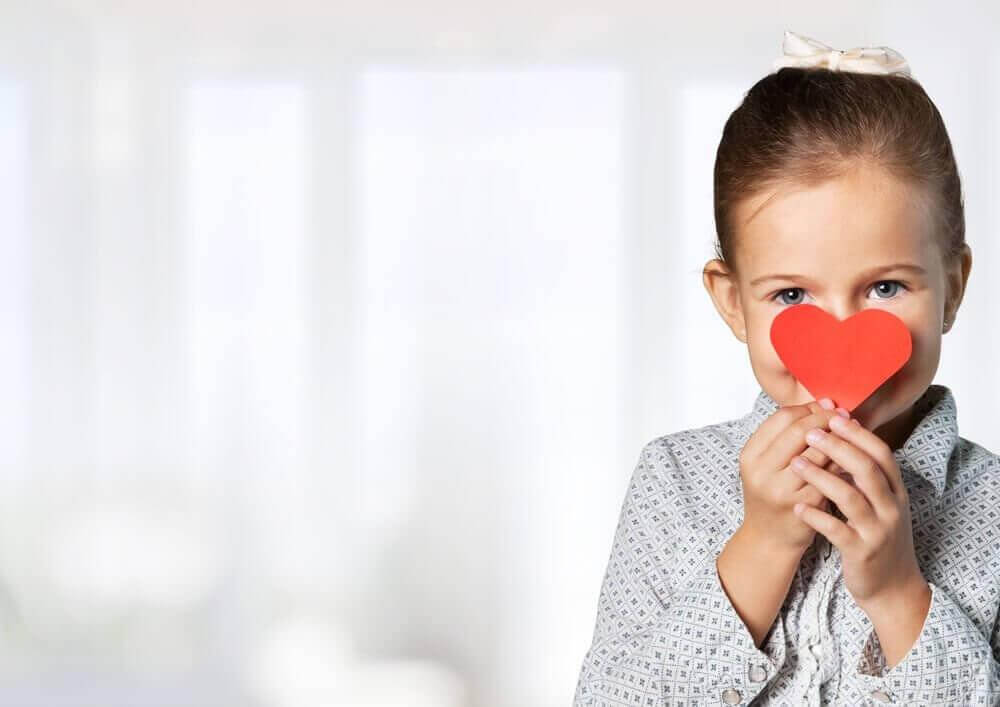 Girl-holding-a-cardboard-heart-in-front-of-her-face
