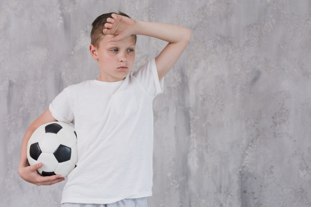 portrait-exhausted-boy-holding-soccer-ball-hand-against-concrete-wall_23-2148186487