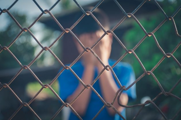 asian-kid-boy-crying-behind-a-metal-chain-wire-mesh-fence-concept-for-child-abuse-human-trafficking_t20_gRxE7G-630x420